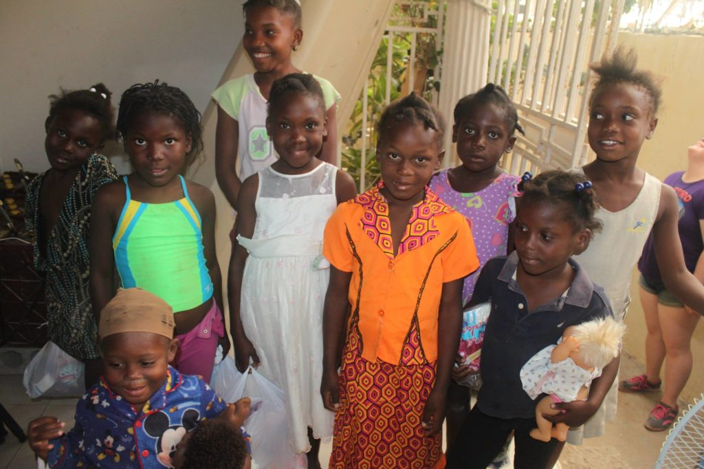 """We typically don't do handouts with teams but because we have been building relationships with these kids for a good while now, had asked their parents permission and knew that these children have so very little materially and no toys. They had asked me for months for dolls and toy cars and I had been telling them for months """"Si Bondye vle"""" (""""If the good God wants"""" which is a commonly used phrase here). I finally got to tell them that I guess God wanted to give them dolls and toy cars because they were brought to my house just for them! There were also some dresses and new undergarments for the girls. I'm still doling out underwear here and there on occasion. Like tonight when I did a scabies treatment on one of the girls and noticed her need for such. The kids were pretty well behaved as they came in to choose their dolls one by one. There were boy dolls too which the big boys were happy to choose but clarified that they were for their baby brothers."""